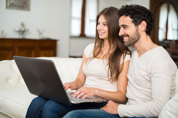 Happy couple using a laptop computer