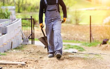 Unrecognizable bricklayer with a wheelbarrow walking