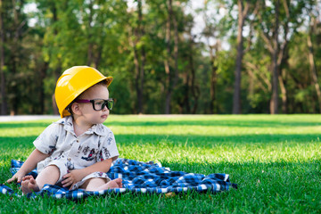 child in the construction helmet sits on a grass playing