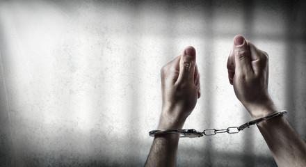 arrest  - man handcuffed in cell prison