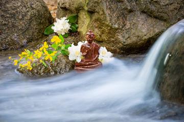 Buddha-Statue mit Blumen an einem Bach