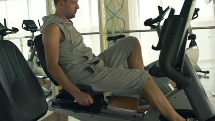 Young man riding stationary bike in the gym