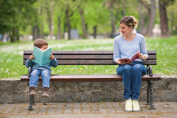 Young woman and cute little boy reading books