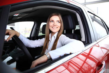 Young woman in her new car smiling