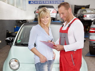 Customer and car mechanic in a garage