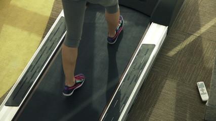 Female legs walking on treadmill machine in gym