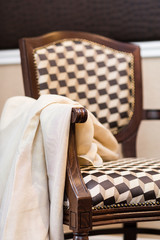 Detail of upholstered stylish wooden chair in brown/beige