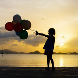 Happy girl with balloons at sunset