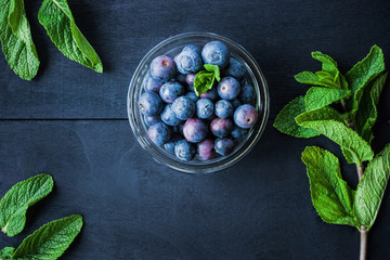 Blueberry in a glass bowl on the blue wooden table