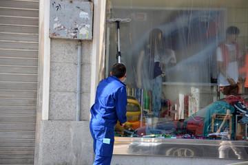 hombre limpiando un escaparate