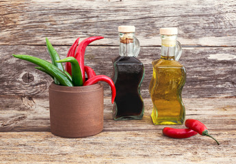 Olive oil and vinegar, chilly pepper. Wooden background.