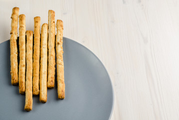 rustic breadsticks in a dish on wood table, close up, background