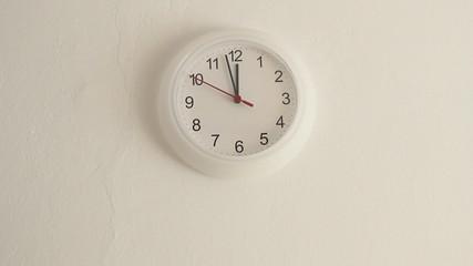 White clock hanging on wall ticking, full HD