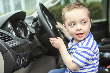 Cute little boy driving fathers car