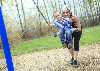 mother pushing son on swing