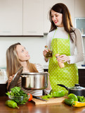 Two happy women cooking  together