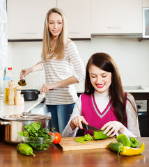 Two young women cooking something