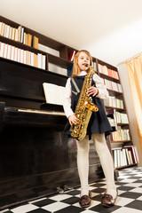 Girl in school uniform plays on alto saxophone