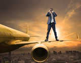 business man and binoculars lens standing on plane wing spying a
