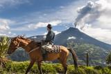 Unrecognizable farmer on a horse front of volcano Tungurahua