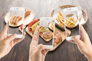 friends using smartphones to take photos of sausage and pork