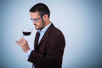 Uomo degusta bicchiere di vino rosso