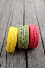 Macaroons colorful delicious on wood background.