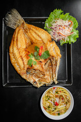 fried fish with fresh herbs and sweet spicy sauce on plate in bl