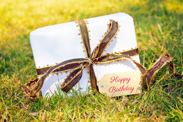 white gift on green meadow - happy birthday
