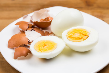 Hard boiled egg with peeled and shattered shells on plate
