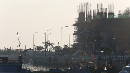 fishing boats by city embankment against building construction