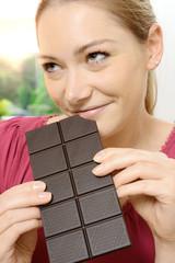 Frau isst Tafel Schokolade