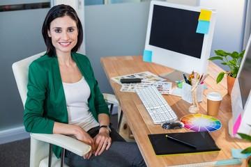 Smiling designer sitting at her desk