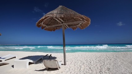 Caribbean beach with grass umbrellas and beds
