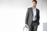 Wyjazd służbowy. Przystojny mężczyzna w garniturze z walizką  poster