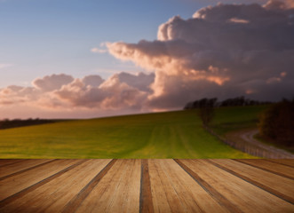 Stunning landscape with stormy sky over rural hills with wooden