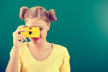 Student girl holding photo camera in front of blackboard