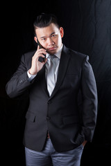 young asian business man talking on mobile phone against black b