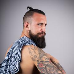 Hipster con brazo tatuado y jersey al hombro