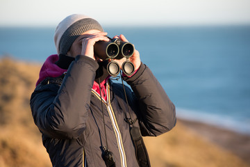 girl looking sea with binoculars