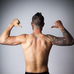 Espalda de hombre con brazo tatuado