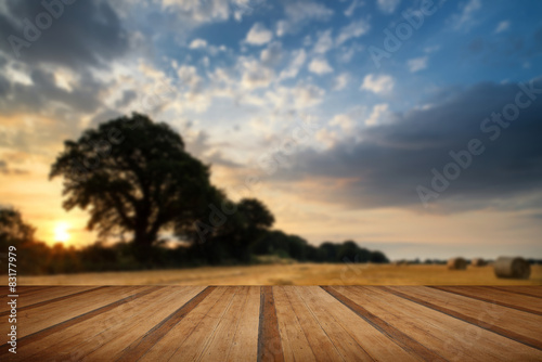 Rural landscape image of Summer sunset over field of hay bales w