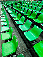 A field of empty green plastic stadium seats.