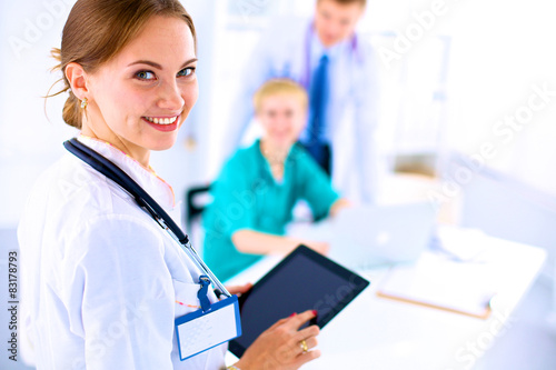 Young woman  doctor holding a tablet pc плакат