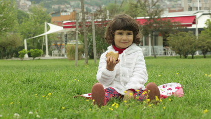 little girl in a white blouse sits on a lawn and eats cake