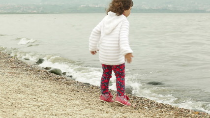 little girl sitting on the beach and throwing stones