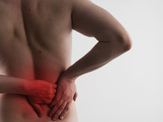 Closeup of male back massaging his sore loin or hip. Health care