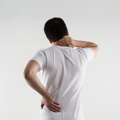 Young male in white t-shirt suffering from neck and back pain