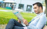 Handsome young man enjoying and reading newspapers