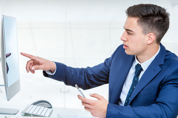 Young businessman pointing at blank computer screen.